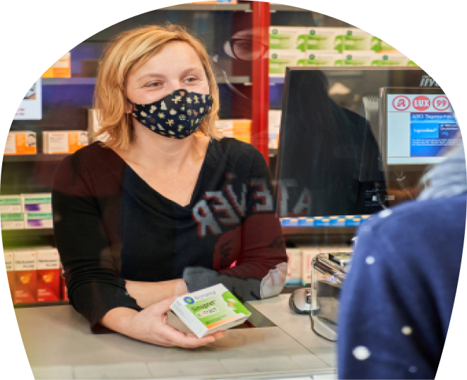 Eine Kollegin mit einem OTC Produkt bedient einen Kunden in der Apotheke LUX 99.